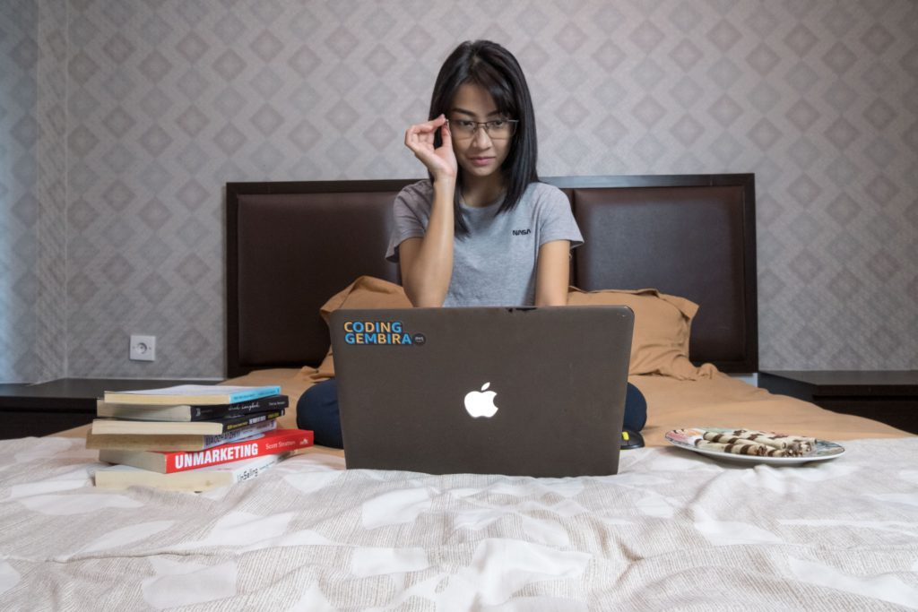 Asian student researching with books and a laptop