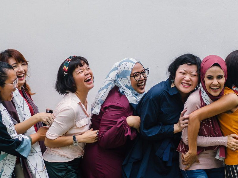 Diverse women laughing and posing for a photo