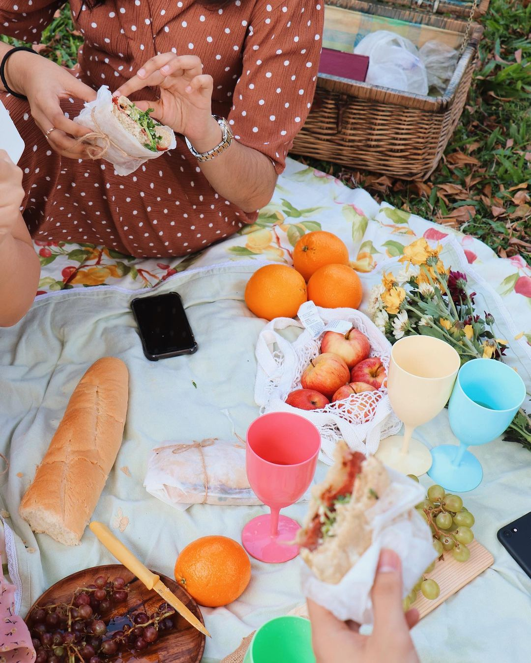 Girls sitting on a picnic blanket and eating