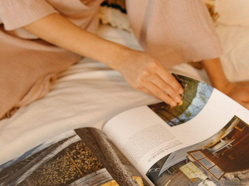 Woman lounging on the bed and reading a magazine